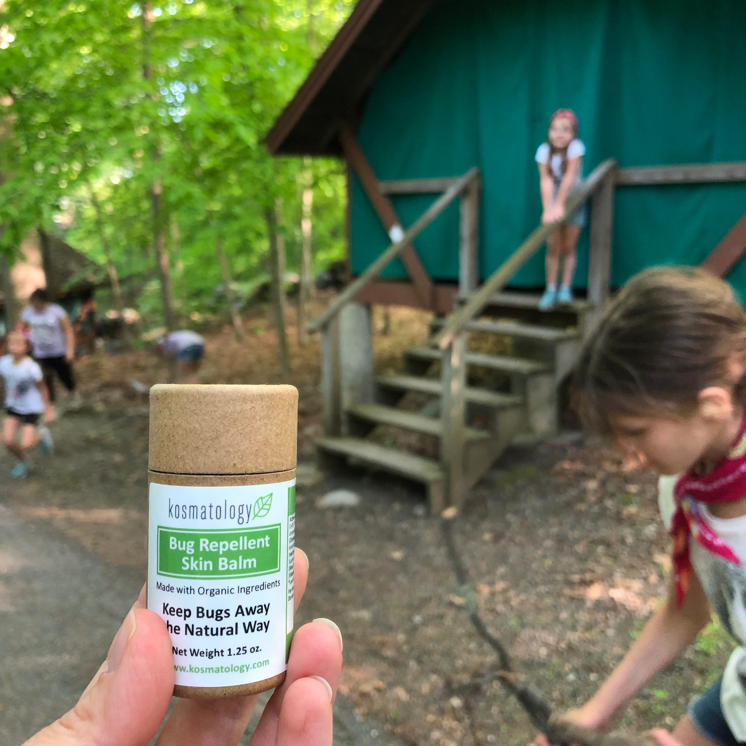 Kosmatology Bug Repellent Skin Balm held by a hand with a tent and children in the background in a wooded area.