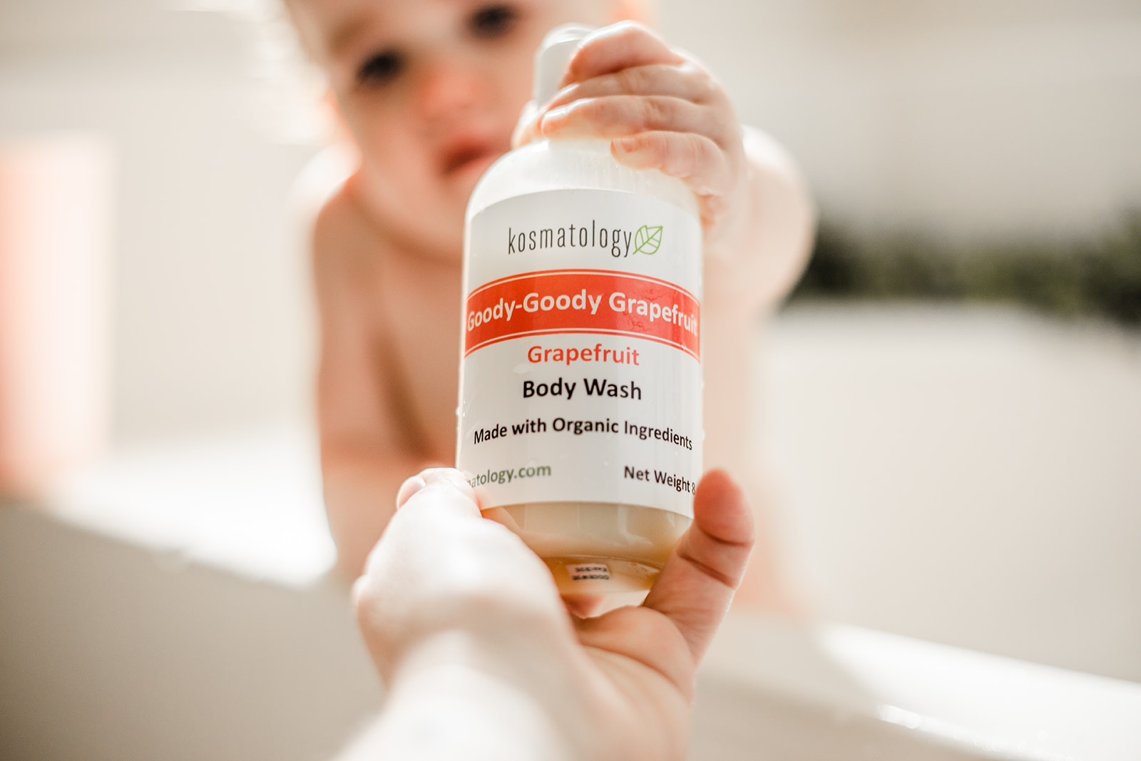 Goody Goody Grapefruit Body Wash with infant reaching out to grab it from mom