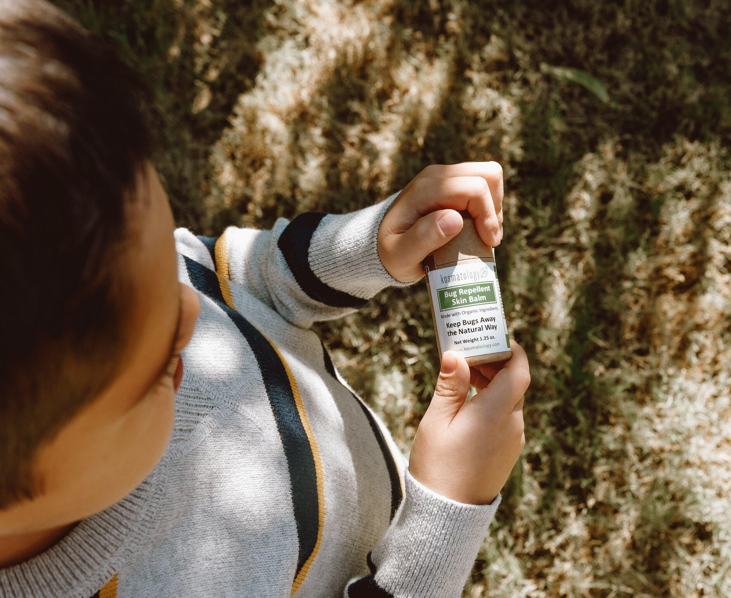 Young boy, standing outside, holding Kosmatology Bug Balm.
