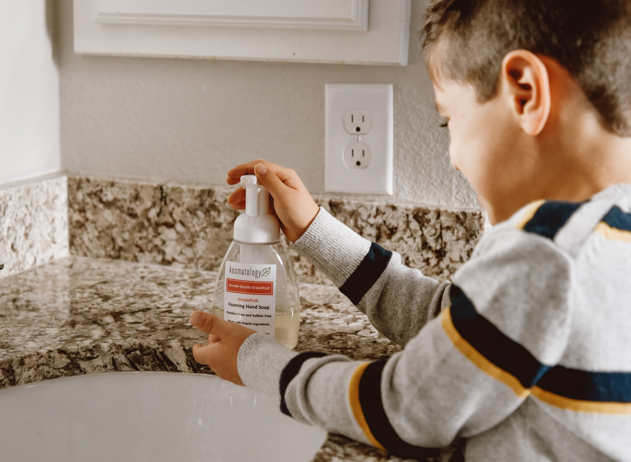 Young boy in bathroom using Goody Goody Grapefruit Foaming Hand Soap.