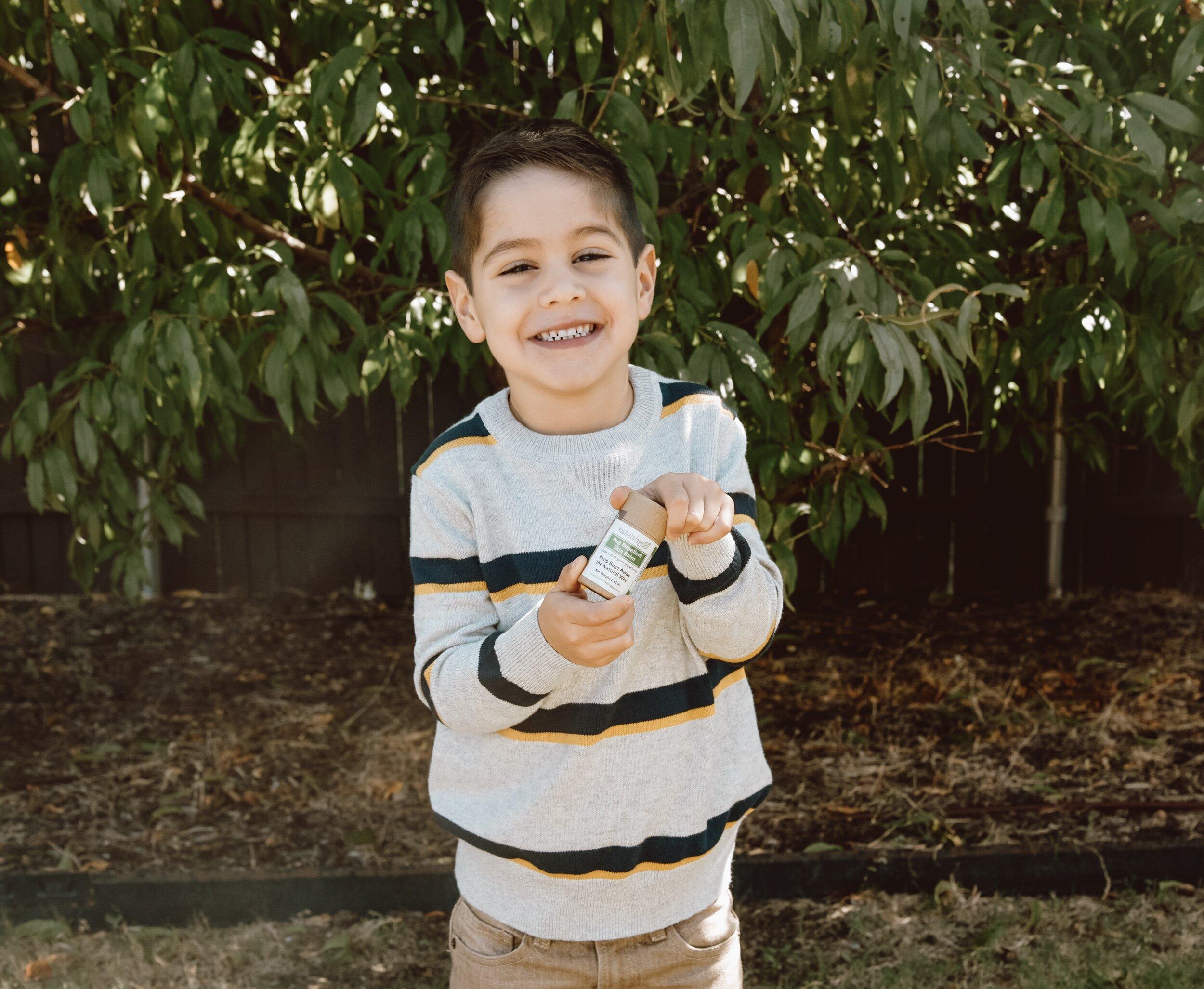 Little boy in striped sweater holding Kosmatology Bug Balm.