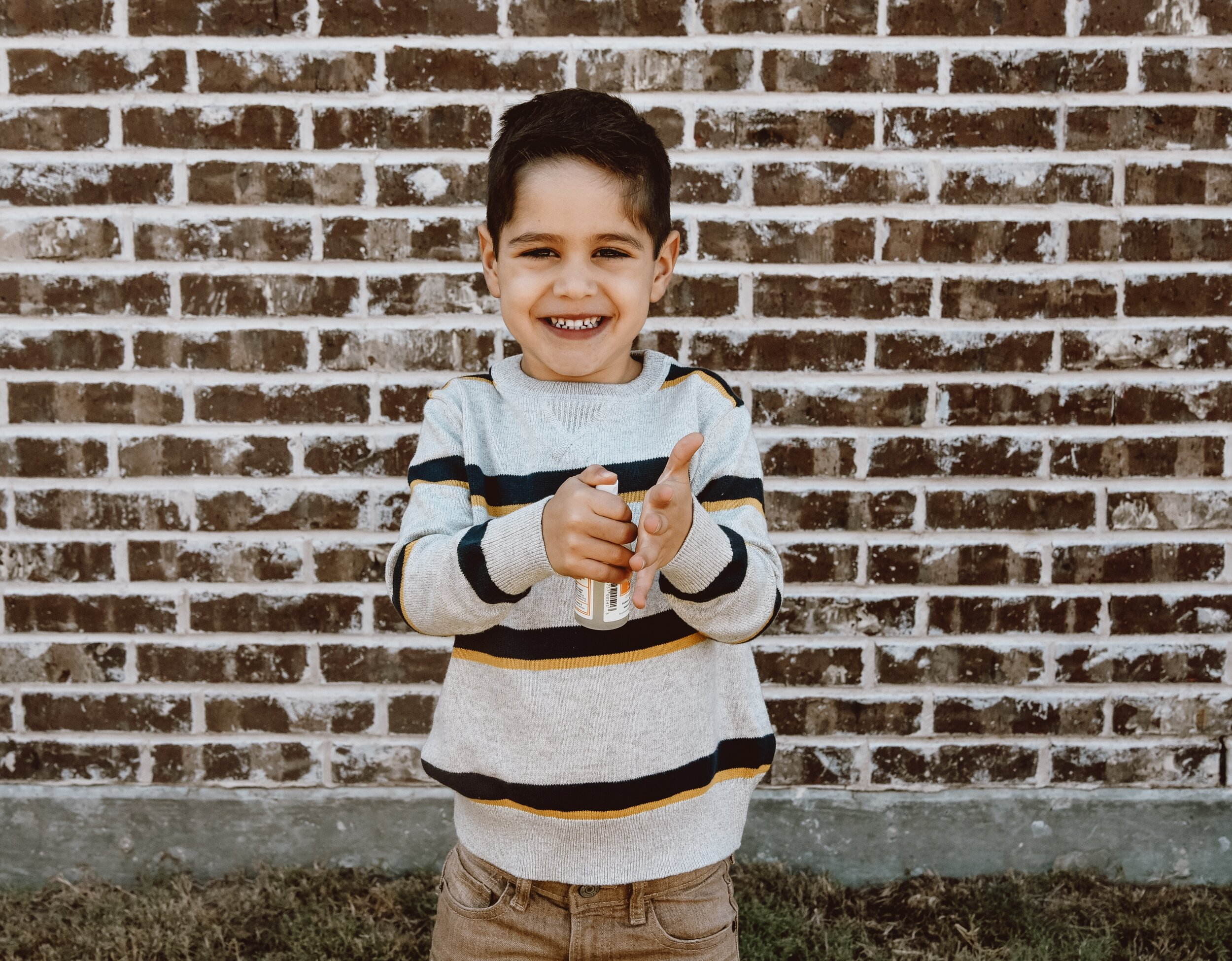 Little boy in front of brick wall using Spritztrus Hand Sanitizer by Kosmatology.