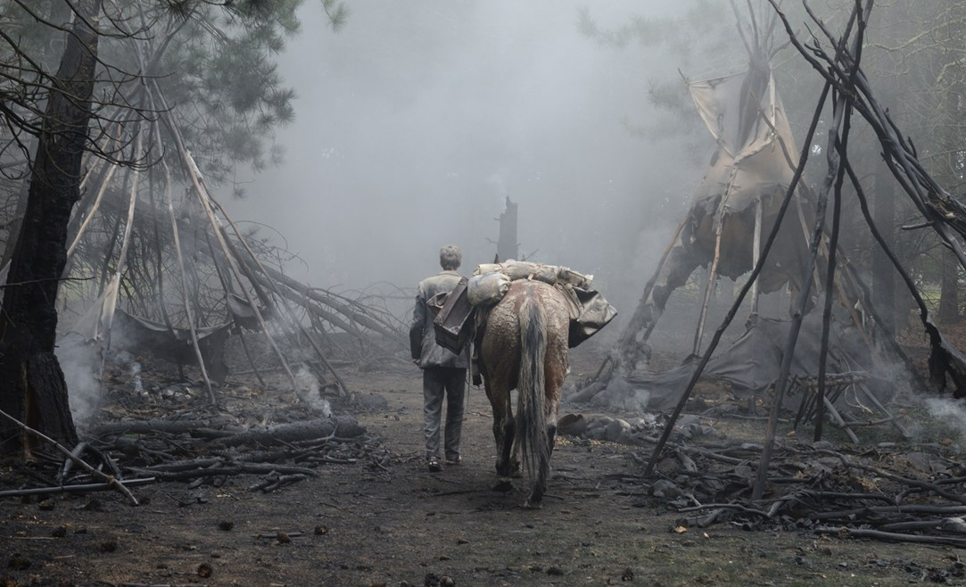Kodi Smit-McPhee wanders the ruins of a native American village in  Slow West .