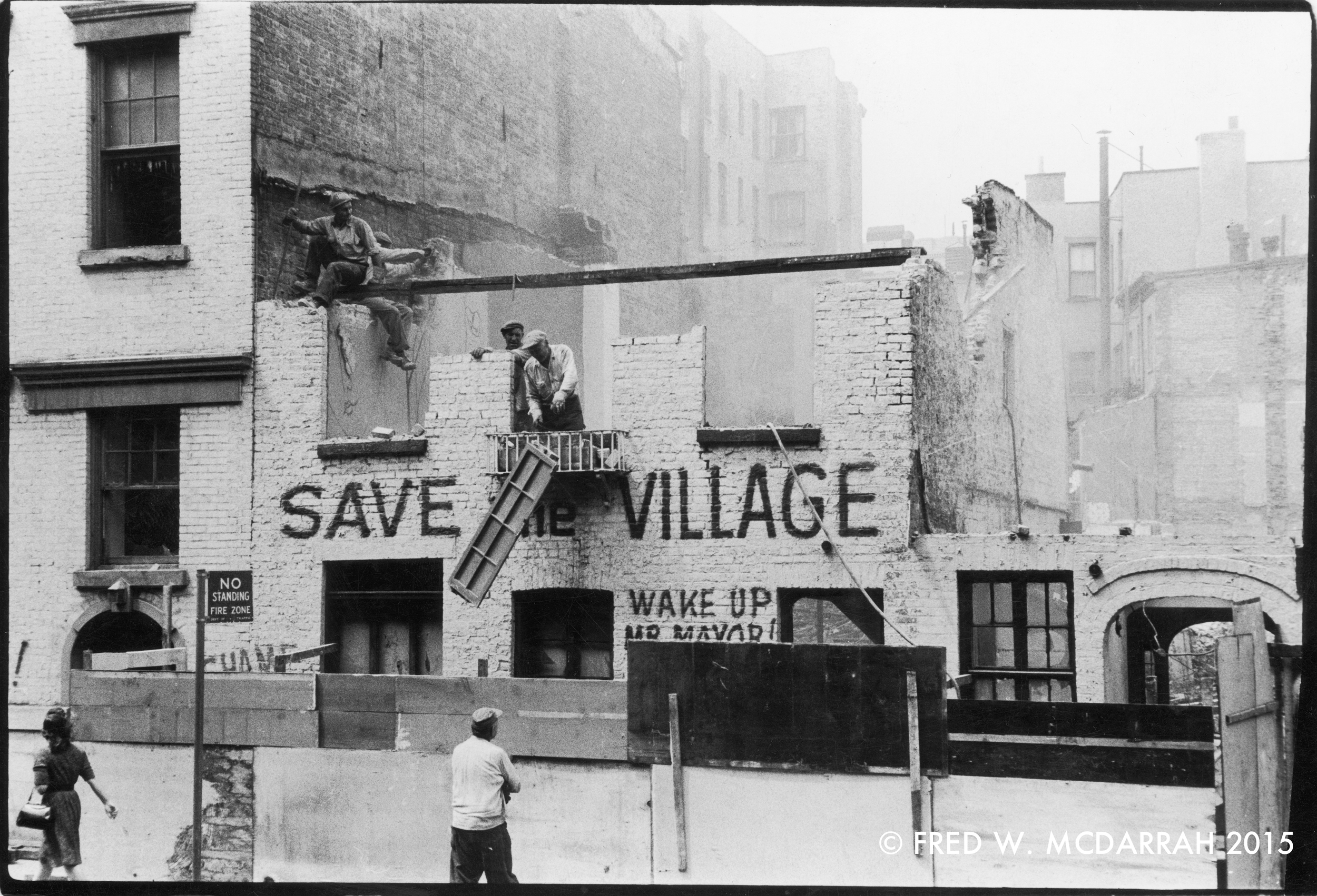 Demolishers dismantle an artist's studio, the facade of which is painted with the slogans 'Save the Village' and 'Wake Up Mr. Mayor!' New York, New York, May 16, 1960. Photo by Fred W. McDarrah.