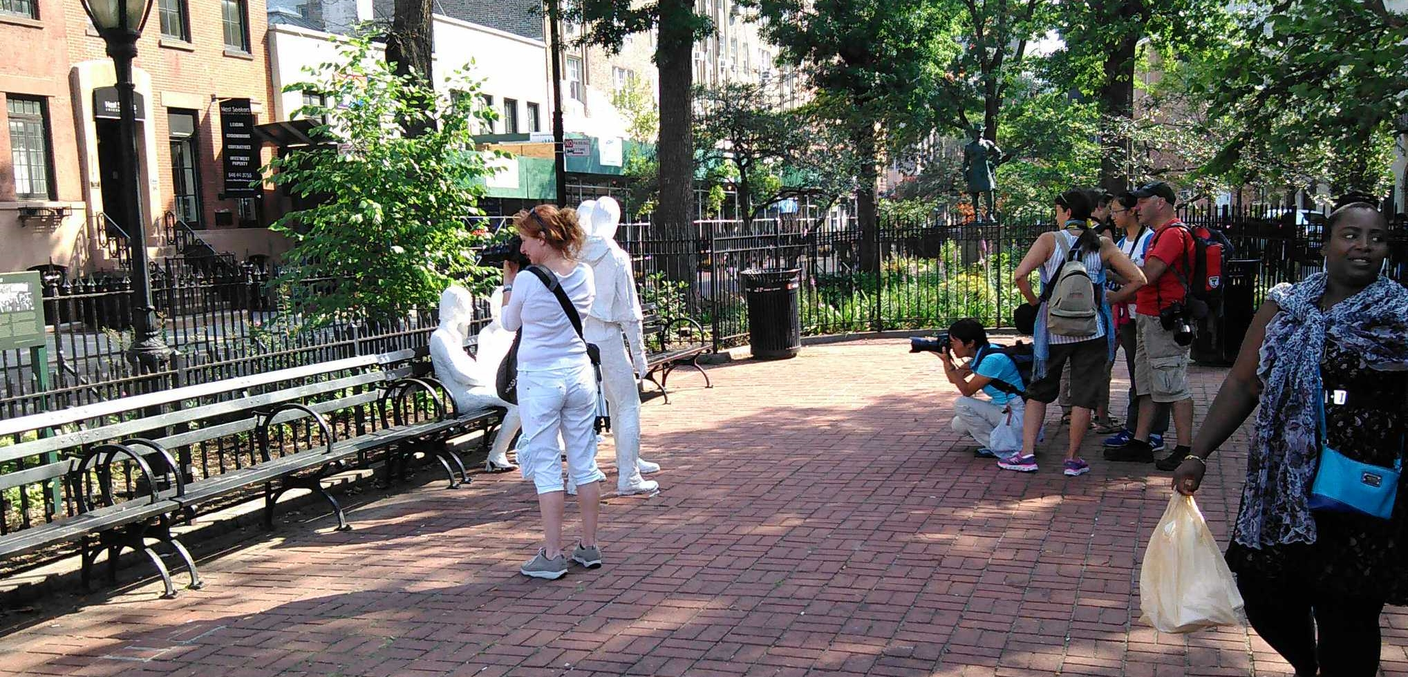 """Tour-goers photograph George Segal's """"Four Figures"""" and the Park Dept. interpretive sign (with Fred W. McDarrah image) at Christopher Park, which lawmakers are now pushing for National Park status. Stonewall is in background with the green scaffolding."""