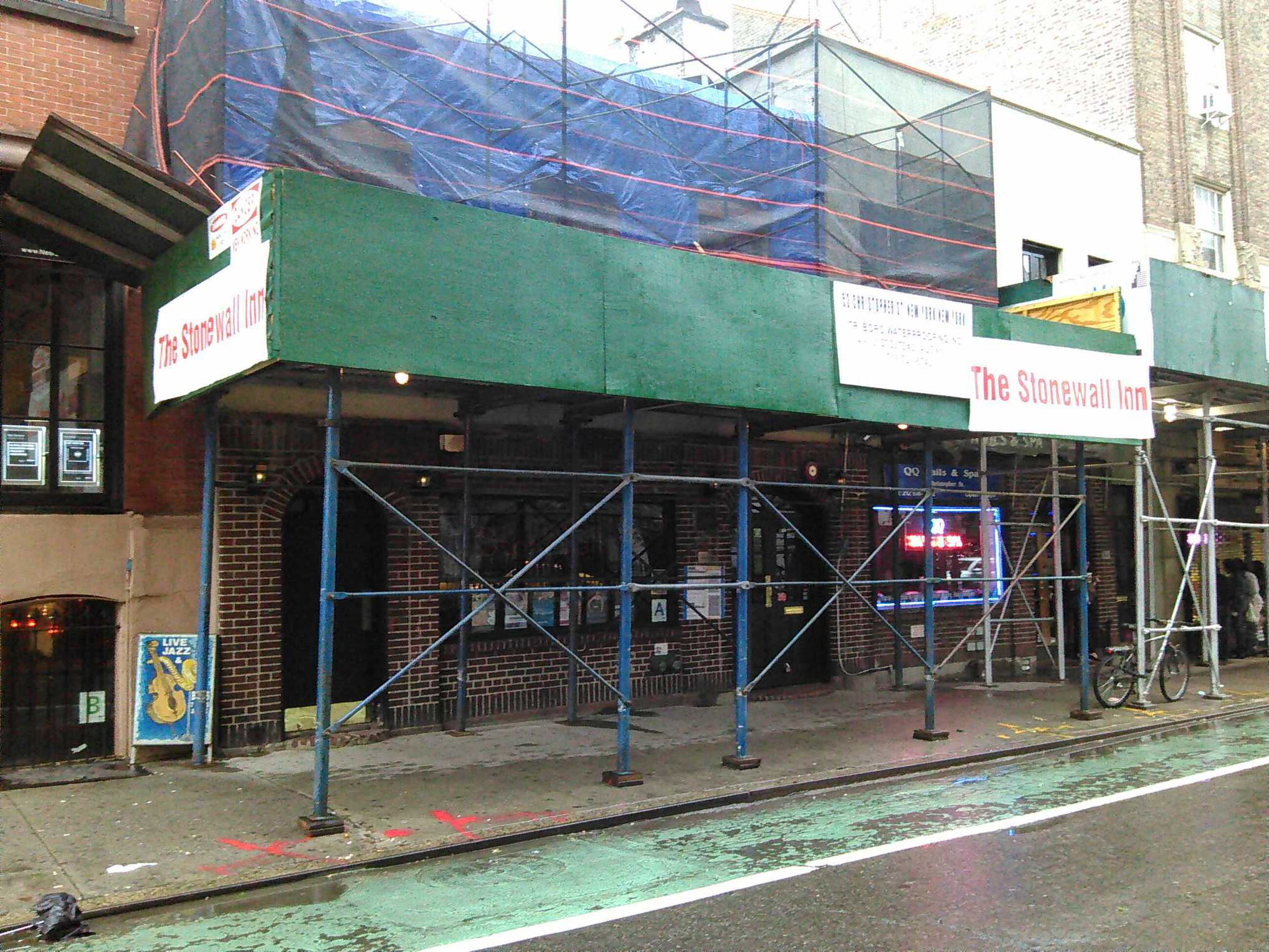 New signs on the green plywood in front of the Stonewall Inn announce what is under the scaffolding.
