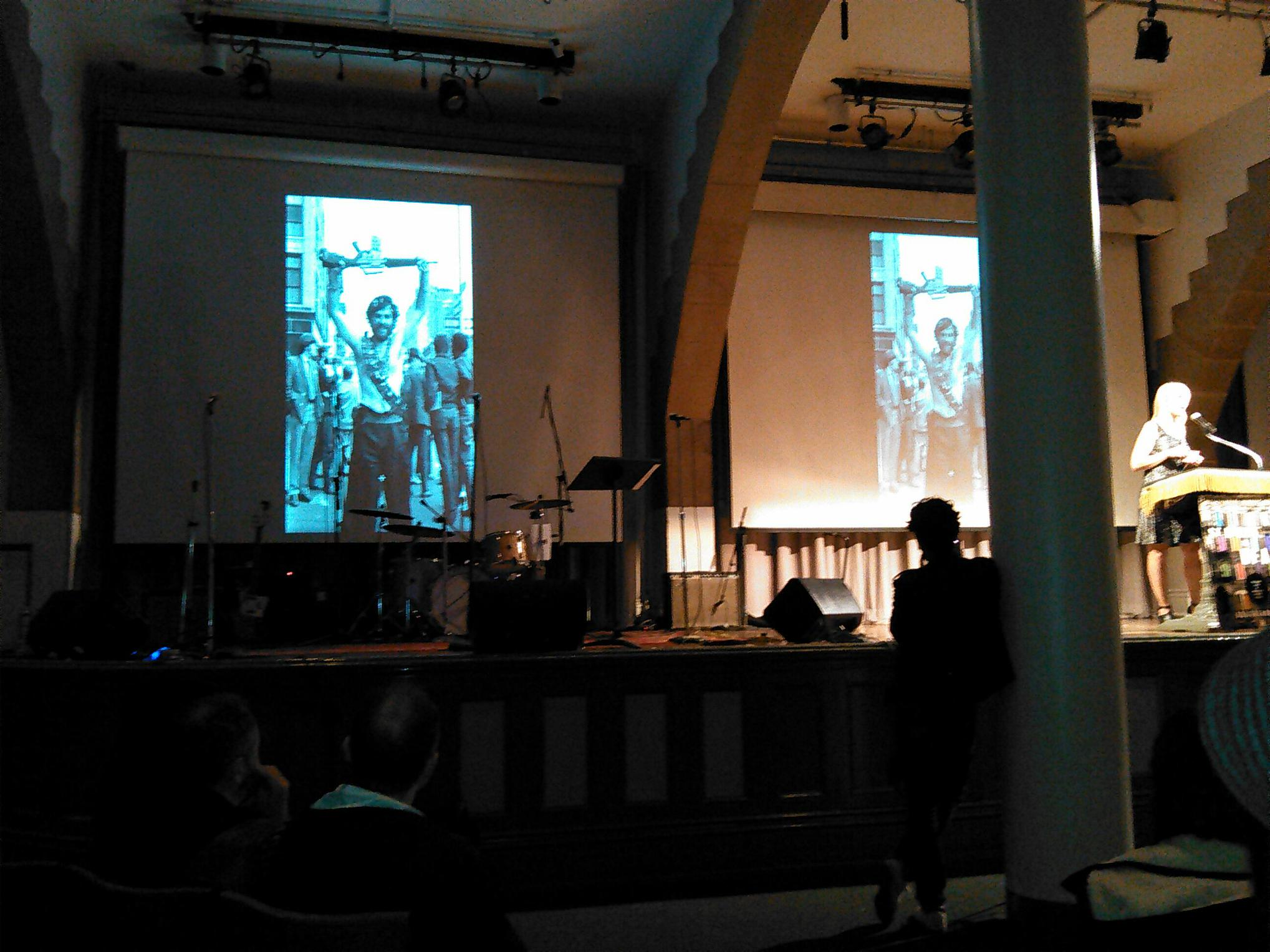 Ada Calhoun on the Cooper Union Great Hall stage with a Fred W. McDarrah image of Jerry Rubin on St. Mark's Place on the screen behind her.