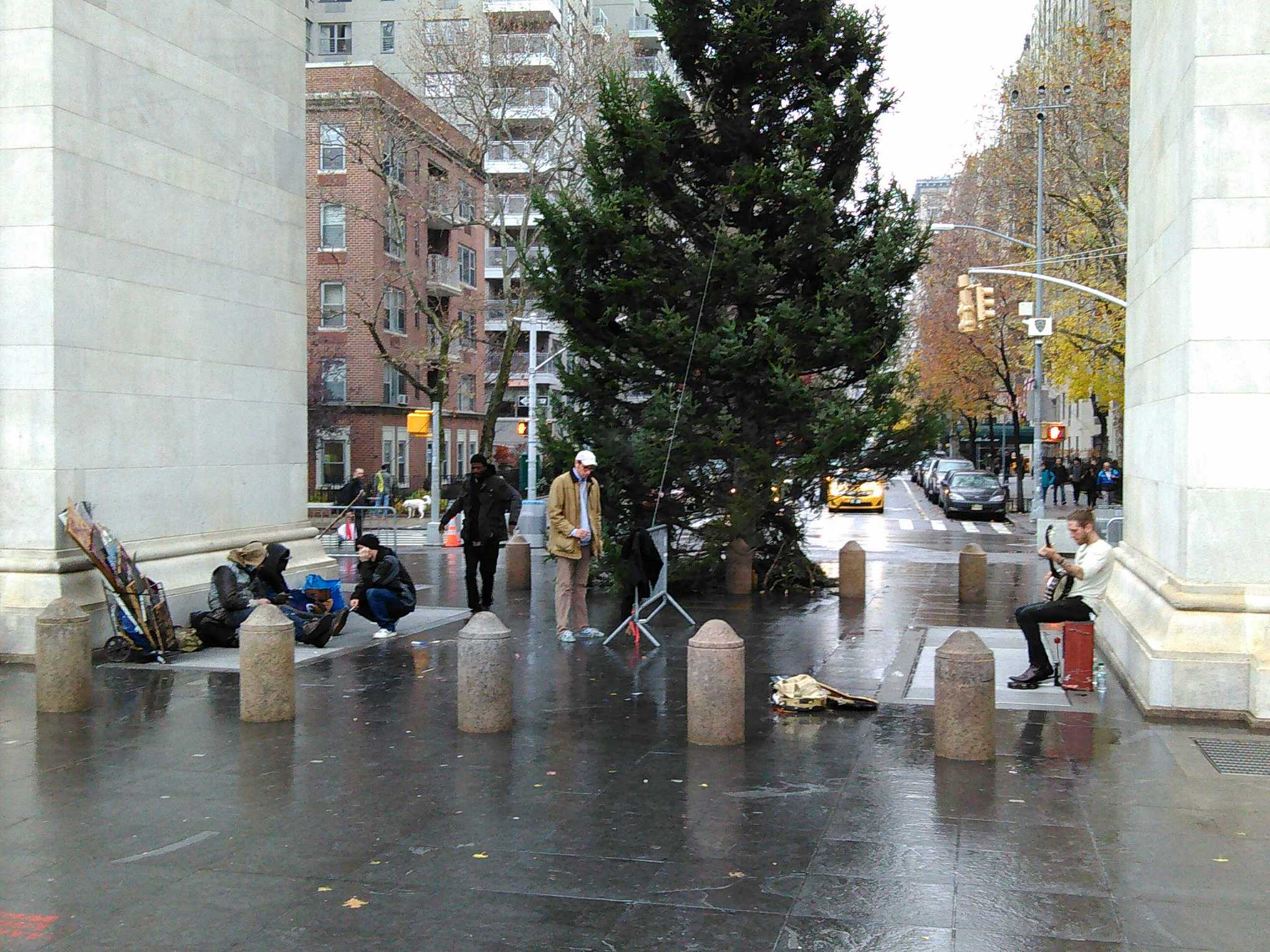 On December 1, the holiday tree was installed, while some street people took up residence on the west side of the arch and a banjo player entertained them from the east side.