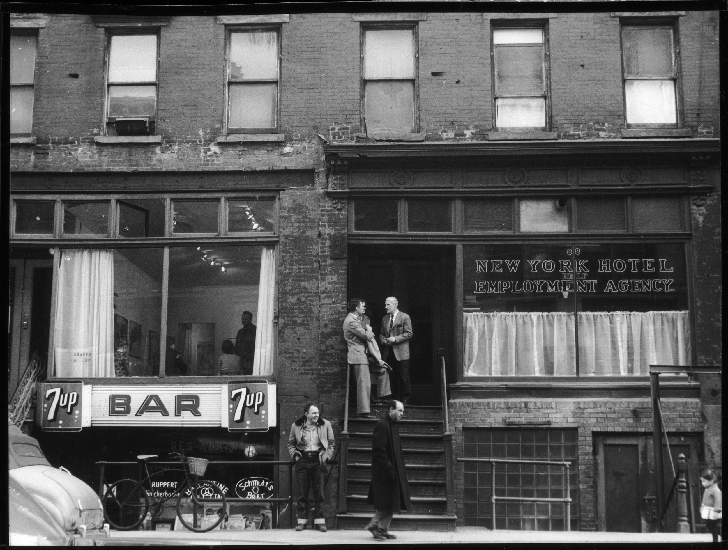 Above: Willem deKooning (1904-1997) (center, with light hair) speaks with author Noel Clad (1923-1962) and his wife at the top of a stoop at 88 East 10th Street, next door to the Tanager Gallery (the storefront above the 'Bar' sign), April 5, 1959. Photo by Fred W. McDarrah. Below: Same stoop, 56 years later. Photo by Save the Village.