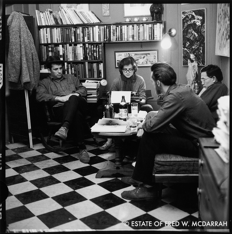 American writers Jack Kerouac (left), Albert Saijo (right, with glasses), and Lew Welch sit around a low table as they collaborate on a poem, which is typed by Gloria Schoffel in the apartment (304 W. 14th St.) of her and her soon-to-be husband, photographer McDarrah, December 10, 1959. The poem was entitled 'This is a Poem by Albert Saijo, Lew Welch, and Jack Kerouac' (later published as 'Trip Trap'), and was based on the trio's journey from San Francisco to New York in Welch's car.
