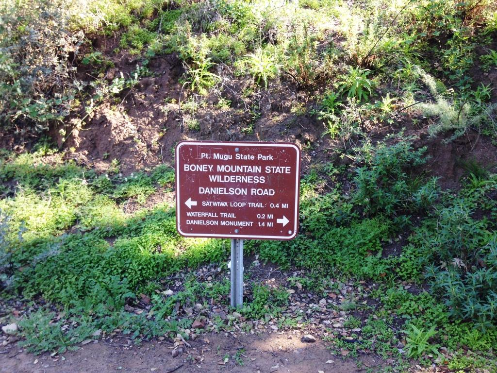 Sign at bottom of hill indicating you distance to waterfall trail and danielson monument