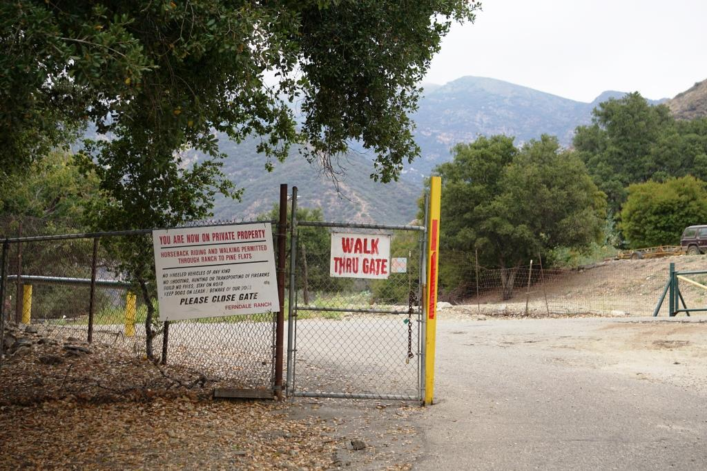 You will be veering left after walking through this gate,  into private property. You will be walking past an oil pump then into an avocado orchard, then past another oil rig (veer left) to the trailhead.