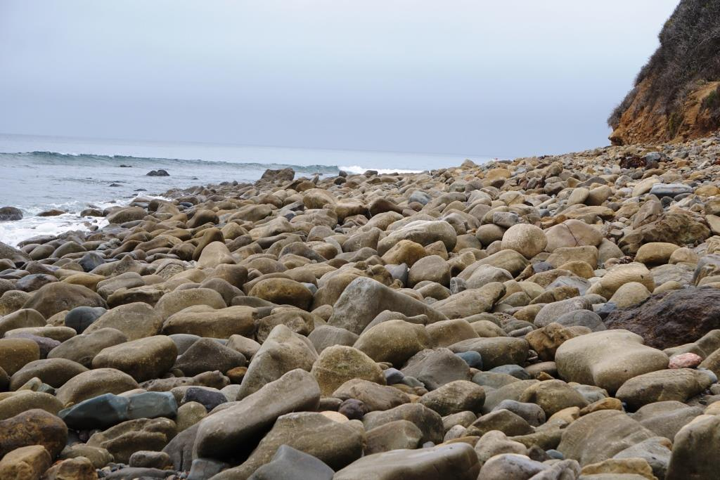Rocks about on the west side of the beach, which stretches around to residences.