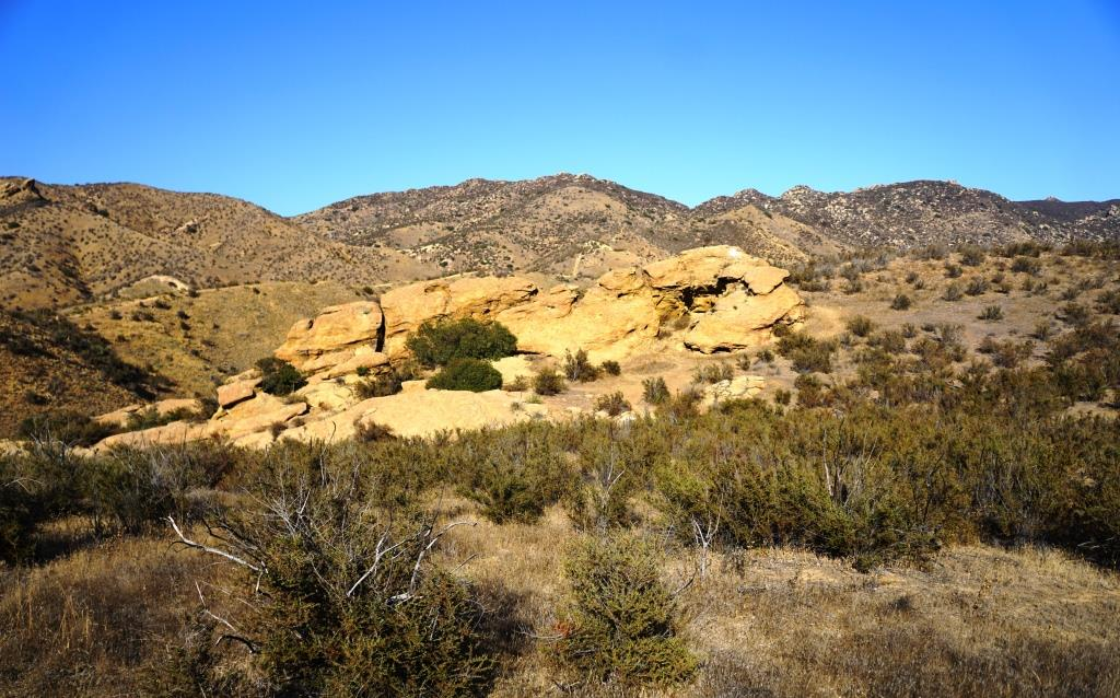 Sandstone formations appear on the upper portion of the trail.