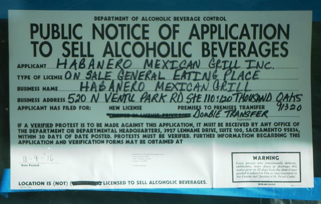 Sign indicating a transfer of a alcoholic beverage serving license has been applied for. It is definitely a must to have a cold beer or margarita with your fajitas.