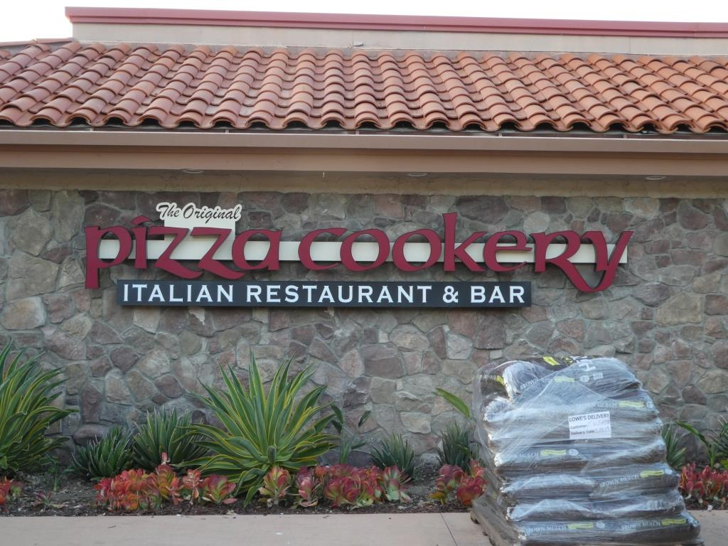 The new The Original Pizza Cookery Italian Restaurant & Bar sign, adorned by fresh bags of brown mulch delivered by Lowe's.