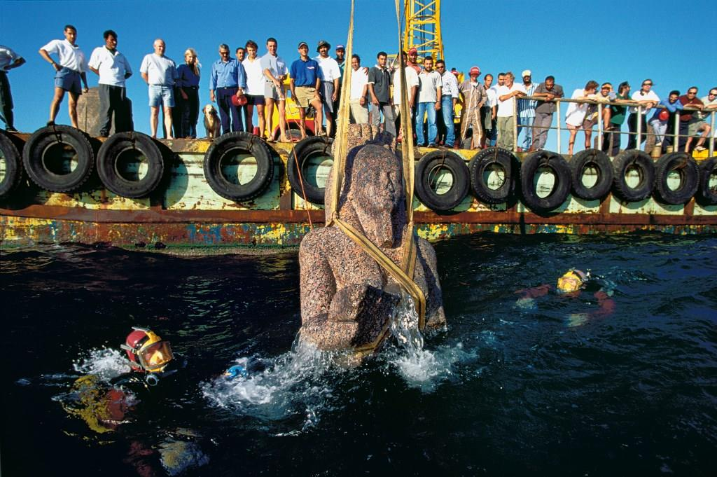The crew of IEASM is assembled to watch the colossal bust of god Hapy being raised, strapped with webbings, for the first time in more than 2000 years out of the waters of Aboukir bay, Egypt.  Photo: Christoph Gerigk © Franck Goddio / Hilti Foundation