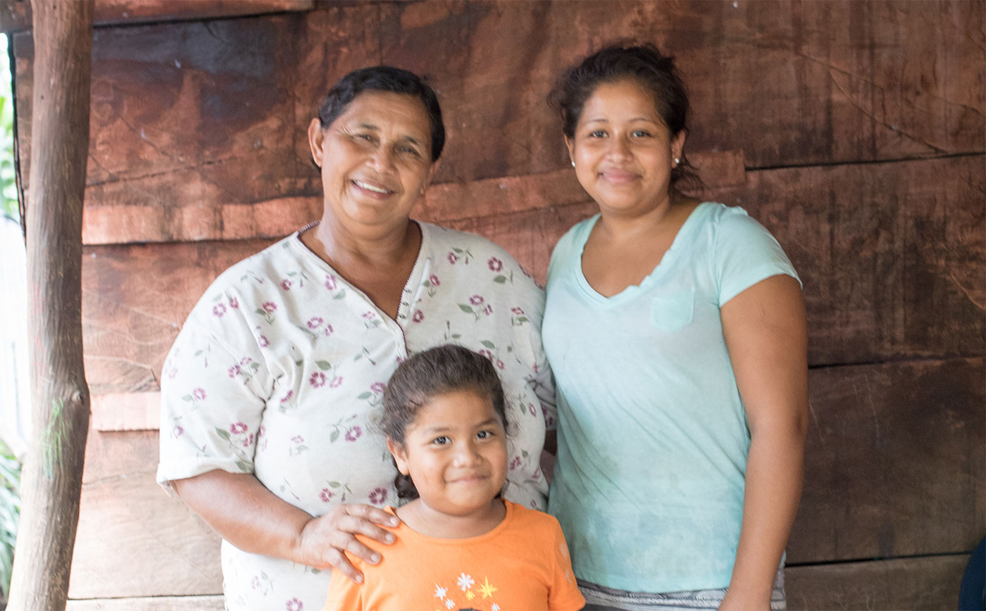 Nora, the bookkeeper of the Gloria Quintanilla Women's Cooperative, with two family members