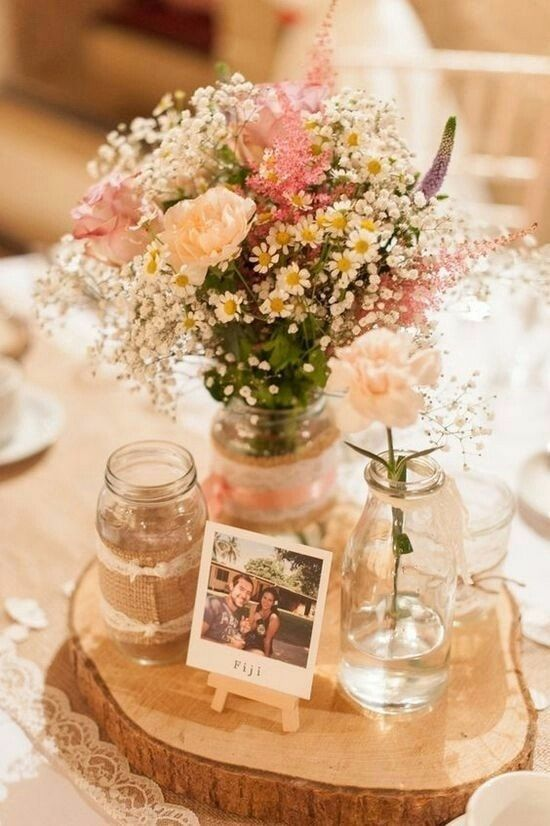 We love the idea of putting a personal spin on your centerpieces! We have seen so many with personal photos or even ones that have you and your partner at the ages of each table! This, paired with some rustic bud vases is the perfect, simple element to your wedding!
