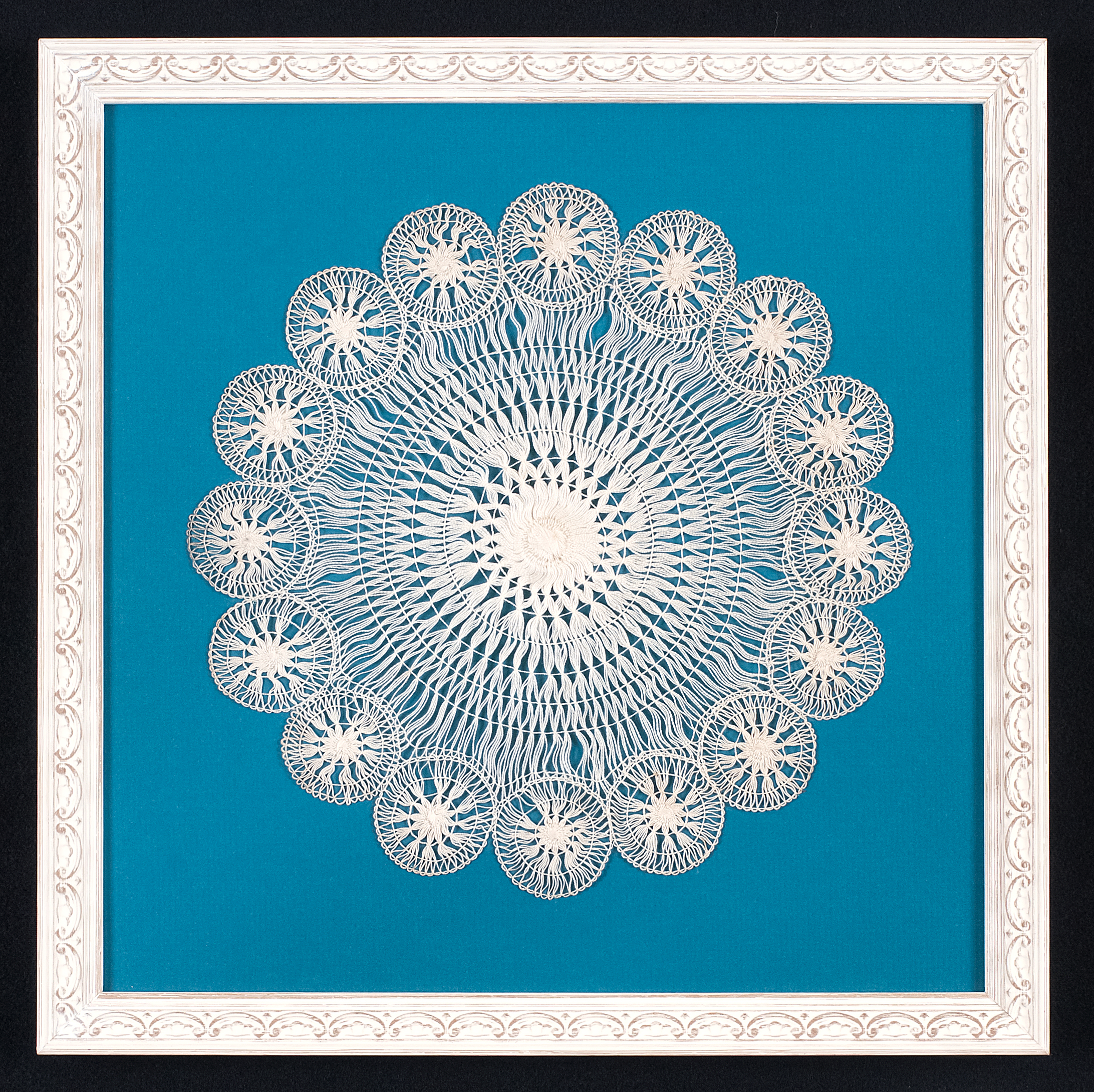 This doily is hand stitched to an acid free mat.Glass spacers are used to lift the ultra violet protective glass off the surface.The frame is a white painted moulding with a floral design. Photo Credit: Elizabeth LaJeunesse  .