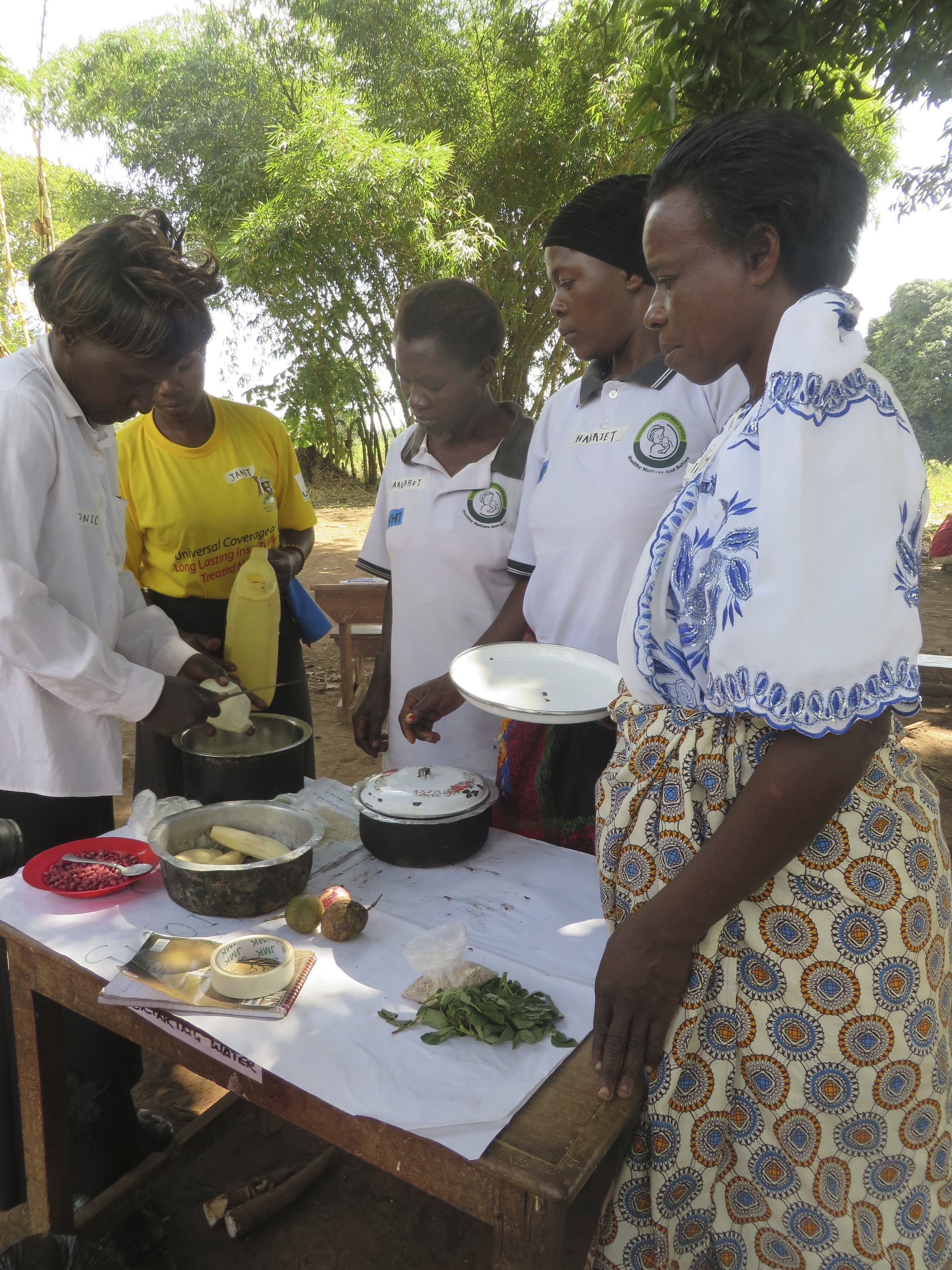 New CHWs look on as Monic demonstrates the preparation of a nutritious meal for infants
