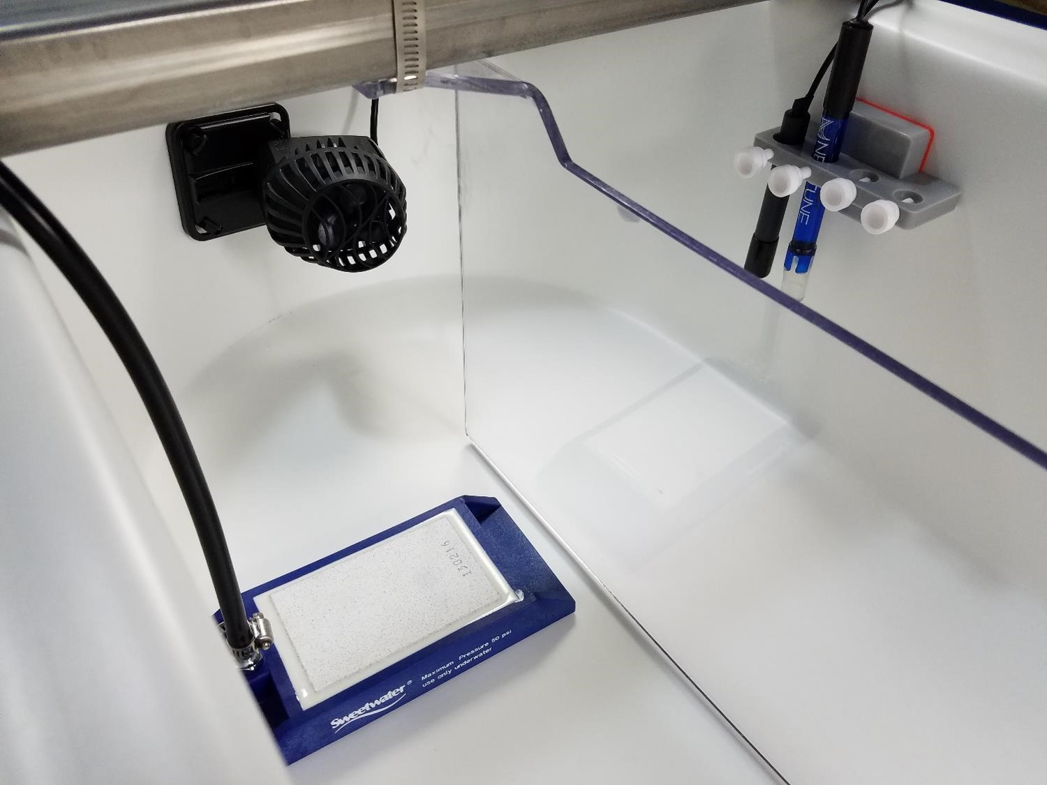 The blue and white block is a ceramic gas diffuser used to sparge a fine mist of CO2 into pond water. The blue sensor probe is a Neptune pH probe (but any pH probe with a BNC connector works). Also pictured is a temperature sensor (black) and the impeller mixer used in the RW0.5i system.