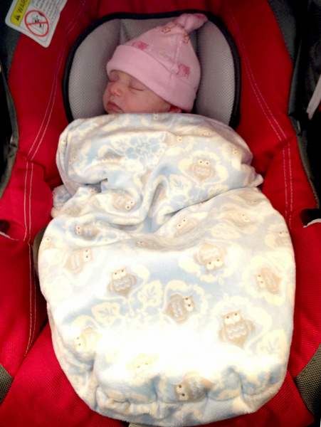 Puffy swaddle applied on top of the straps and tucked around body. Carseat shown is Chicco Keyfit 30 with infant insert.