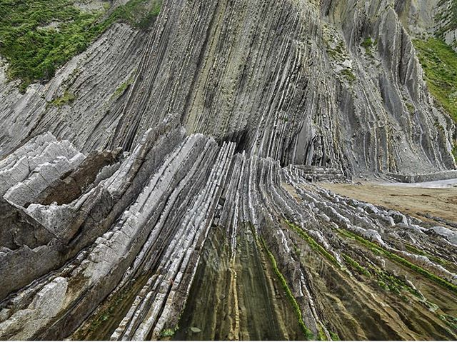 "Strata on the Y and Z axis - 60 million years of Earth's History. . . BASQUE COAST UNESCO GLOBAL GEOPARK (Spain) ""Spectacular coastal formations marking various chapters of the history of the planet"" 🌍💚 . . The coastal outcrops, a 5000 m thick flysch deposit, of the Basque Coast UNESCO Global Geopark reveal, layer by layer, a practically continuous record of some 60 million years of the history of our planet, including several ancient global crises and catastrophes. One of these layers marks the last of the five mass extinctions to have taken place over the course of the Earth's history. -UNESCO . . 📸 @edwardburtynsky"