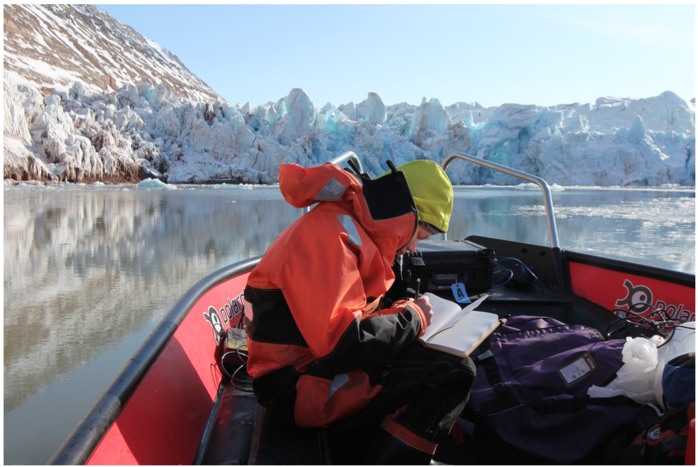 Kristin Schild in her survival suit and field gear collecting samples out of a Rigid Inflatable Boat (RIB) in Kongsfjorden, Svalbard, Norway. She is studying the influence of a warming climate on ice discharge and its influence on physical and biological dynamics within the fjord. Photo: K. Lindbäck