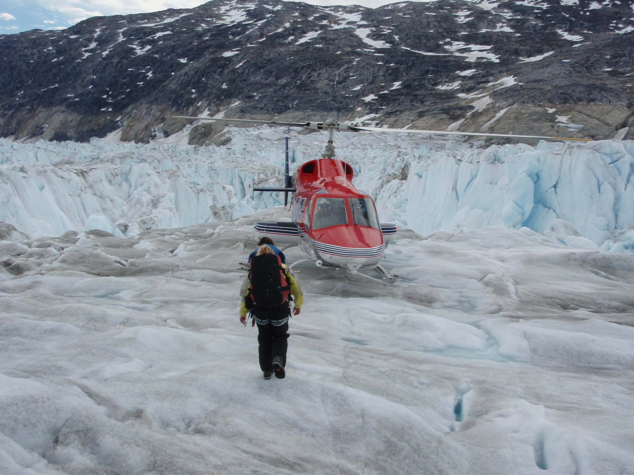 Kristin Schild headed back to the helicopter after installing a high resolution GPS on Helmheim Glacier (Greenland, 2009). Photo: Gordon Hamilton