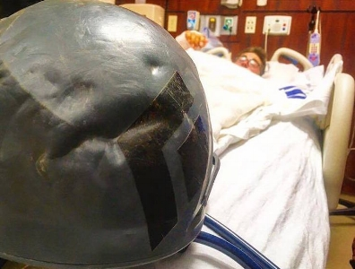 Gorder in the hospital with the dented helmet that he believes saved his life or prevented a serious head injury.