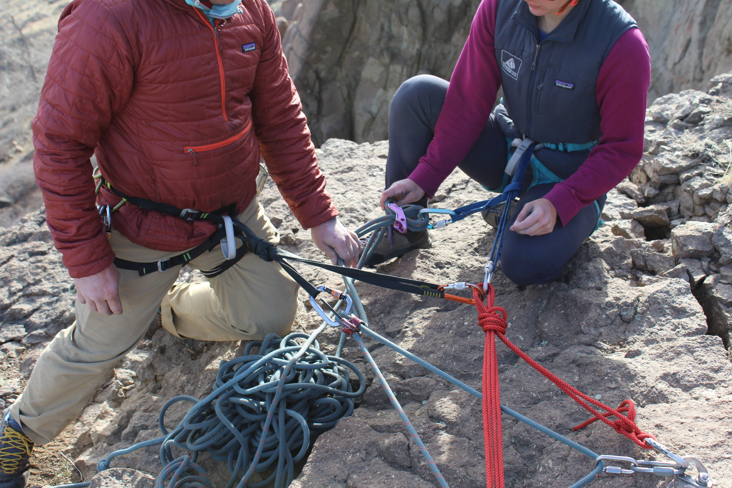 With their back turned towards a precipitous cliff's edge and their attention focused on setup tasks, these climbers are using technical security (a tether and locking carabiner) to stay secured during setup.