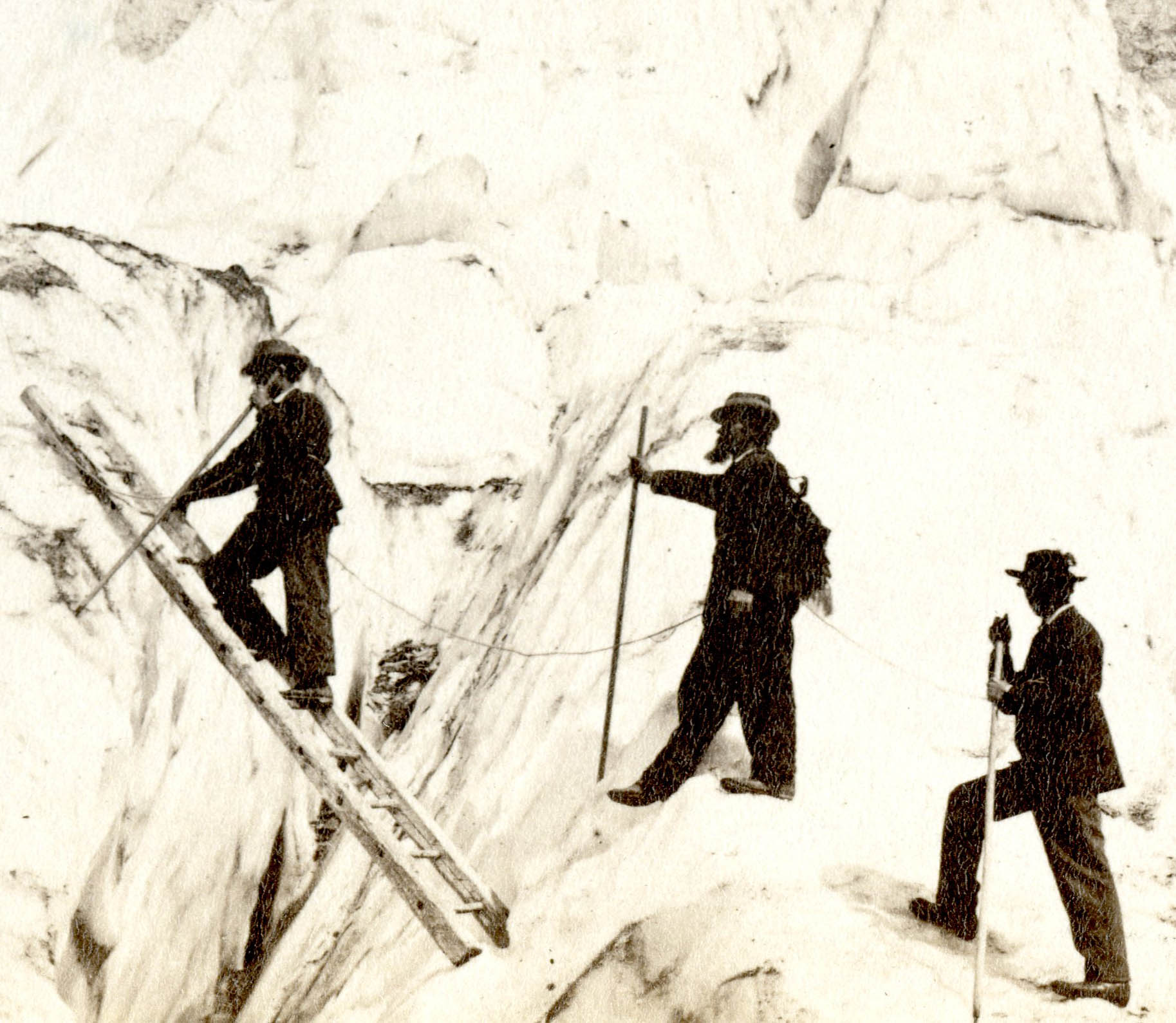 An 1870's photo of men using original alpenstocks to cross a crevasse in the Alps. These alpenstocks have no cutting tools.