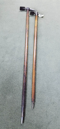 Two alpenstock, full length, with the cutting implement at the top and ice pick at the bottom.