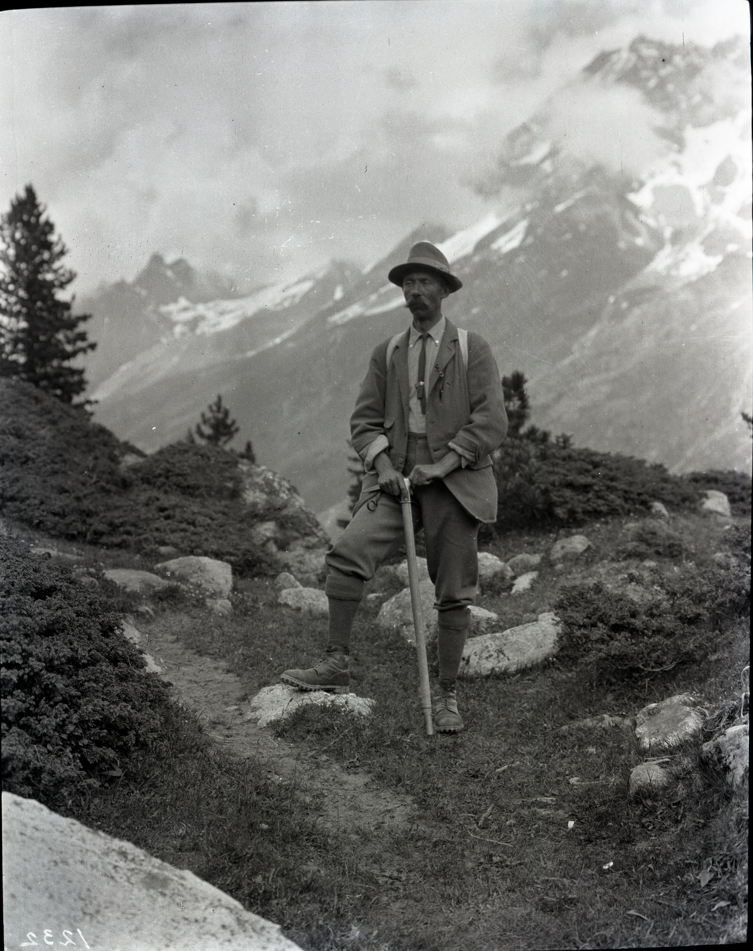A mountaineer resting his hands on his ice axe while on the trail. From the Andrew James Gilmour collection