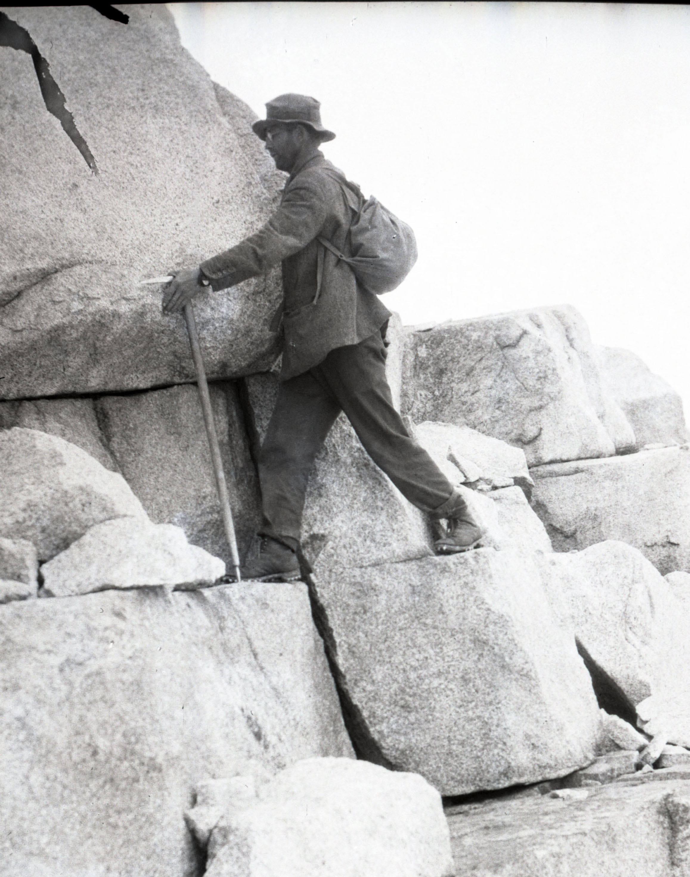 A climber ascending a rock face, using his ice axe as a walking stick. From the collections of the American Alpine Club.