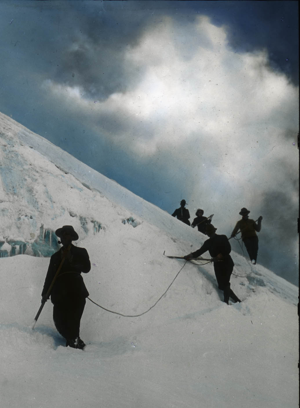 A climber anchoring himself with his ice axe - This photo is from our lantern slide collection
