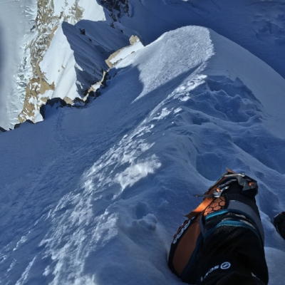 Looking down a knife-edge snow ridge on the Cassin.