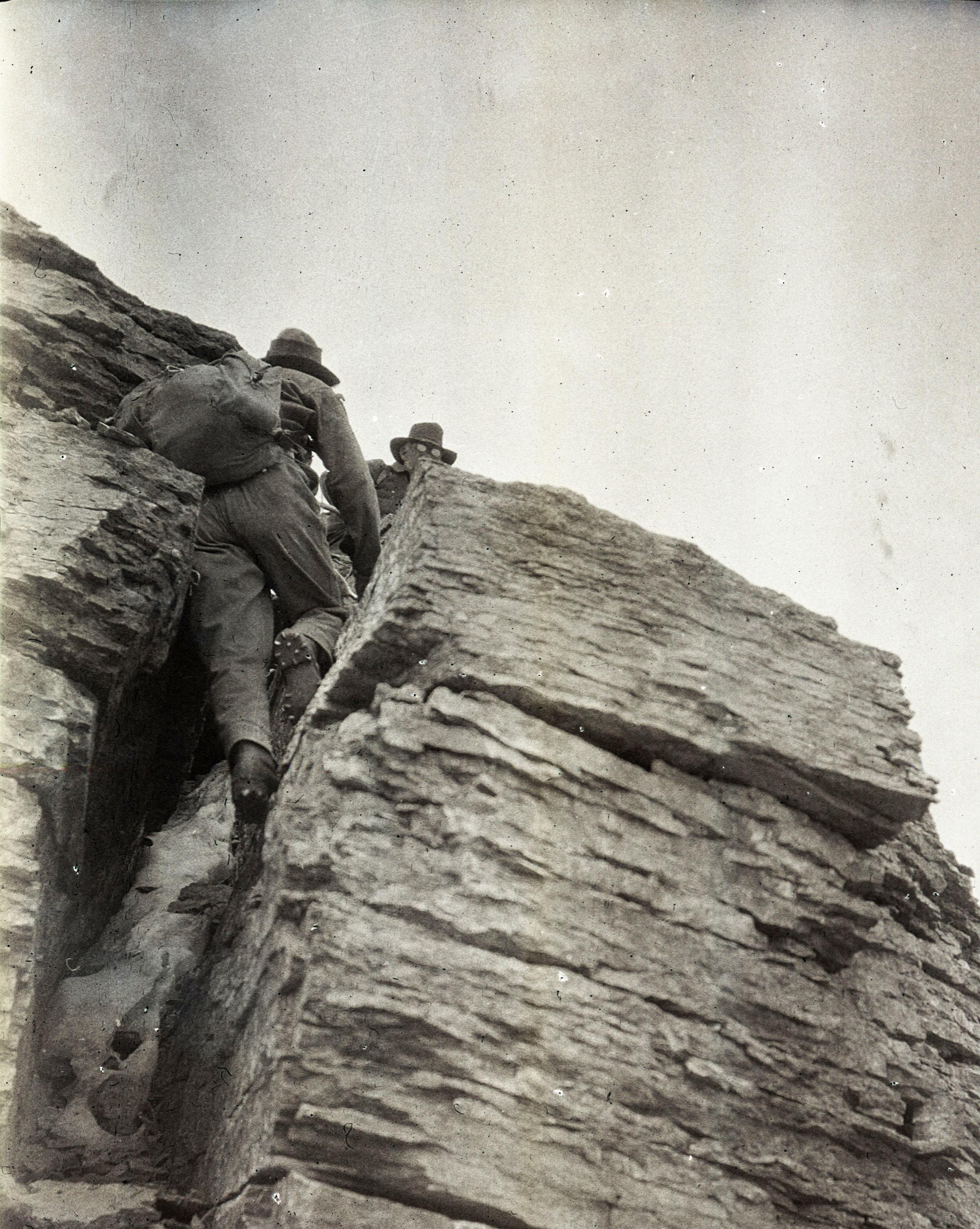 Climbers in a crack near the top of Mumm Peak, Canada