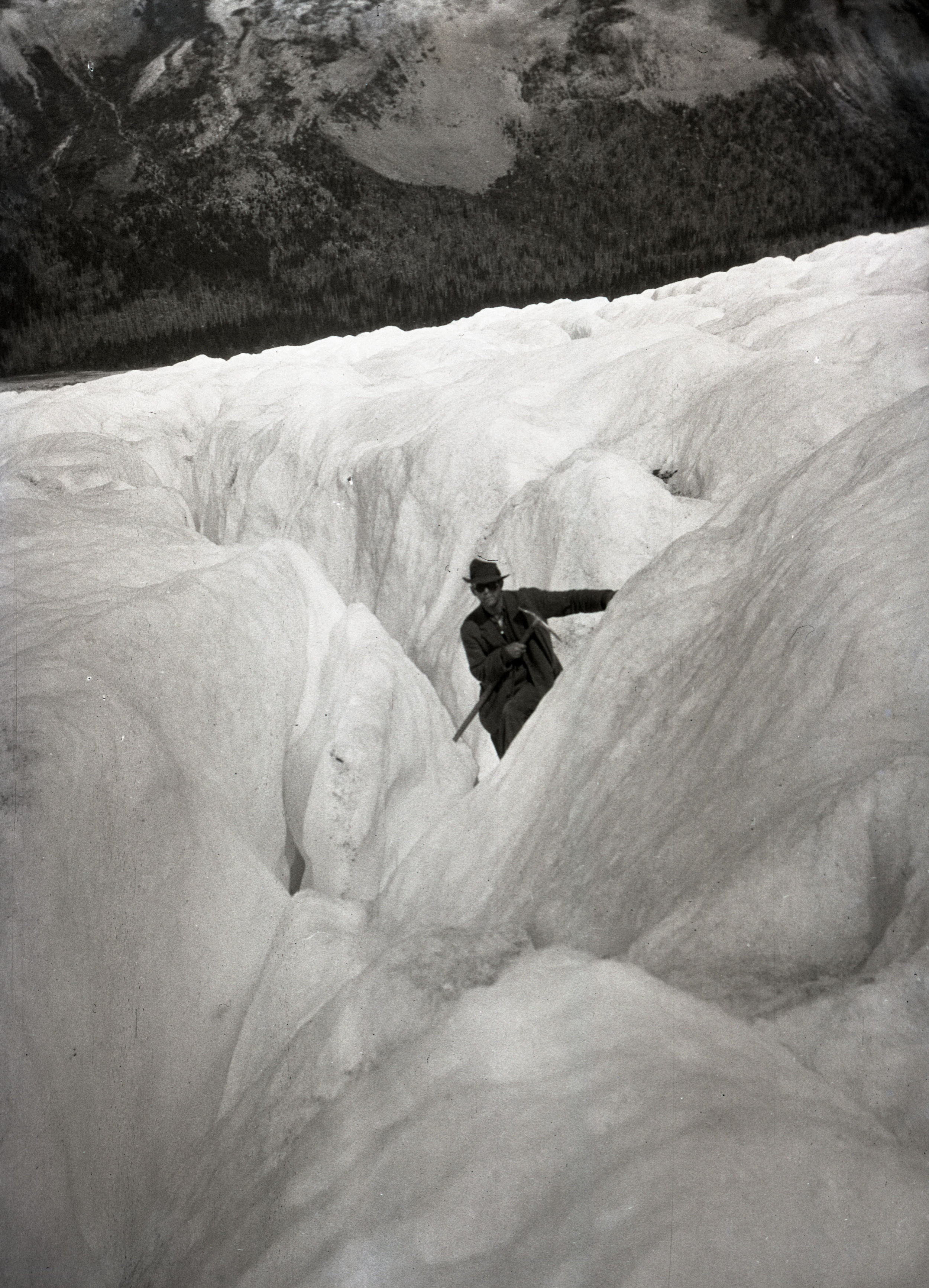 A man making his way through a crevasse on Robson Glacier, Mount Robson
