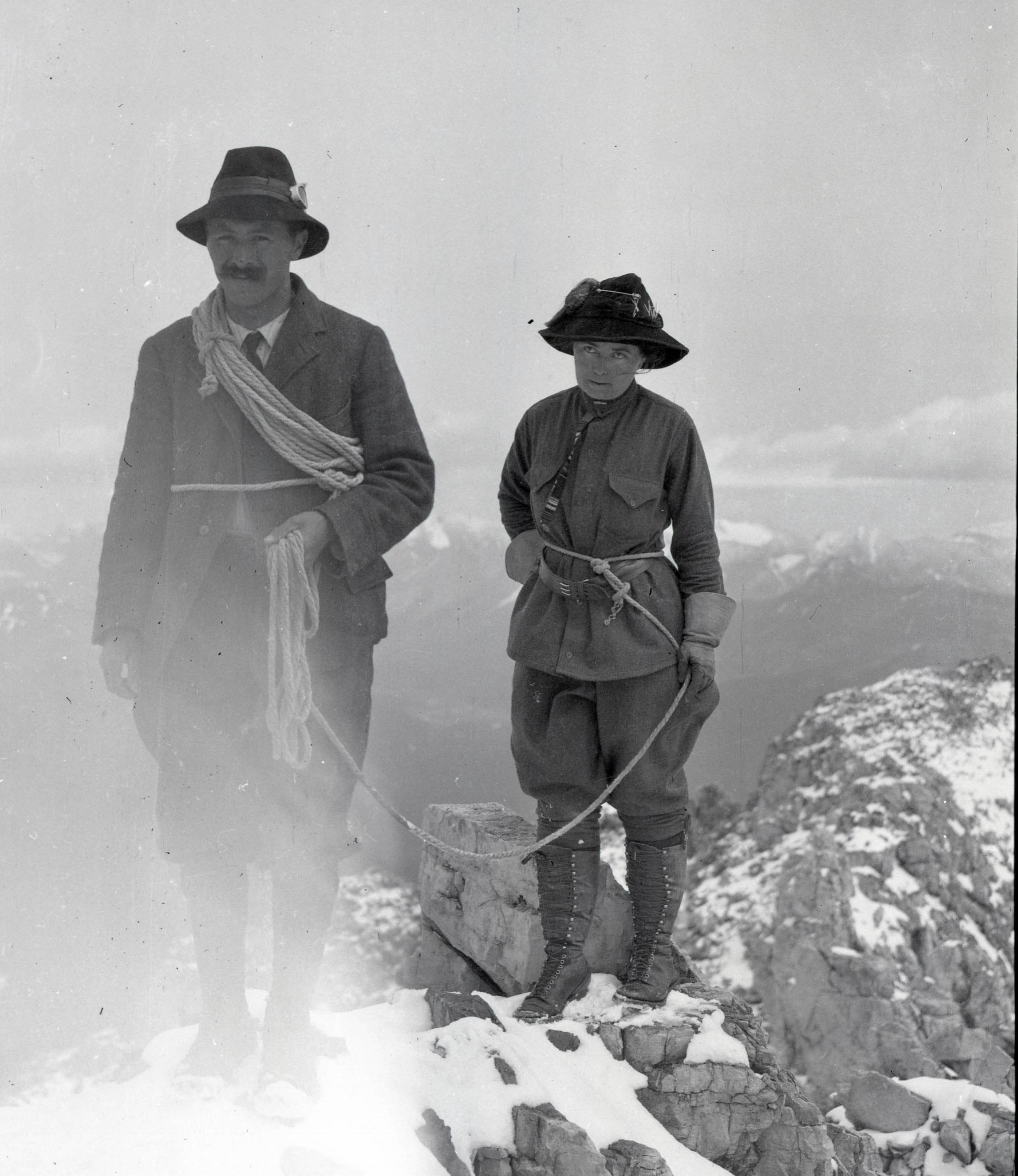 A man and woman celebrating on a summit.