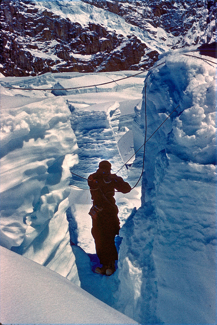 Off came out packs and snowshoes, and soon Bill was cutting his way down into the   crevasse. Ten feet down, and he was gingerly dancing across a six inch vane of ice to the wedge. Another ten feet of vertical climbing on rotten ice and he hauled himself onto the flat top of the wedge.