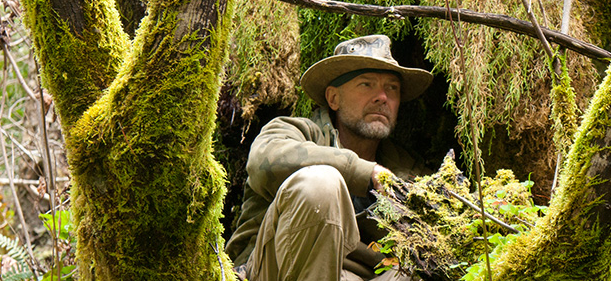 """Survivorman"" Les Stroud, with a close-cropped salt-and-pepper beard, sits in a large moss-covered tree. Photo from OLN website."