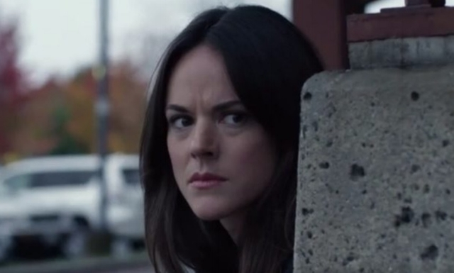 "In a still from ""Woman On the Run,"" dark-haired Nomi Gardner (Sarah Butler) looks intently from around a concrete corner."