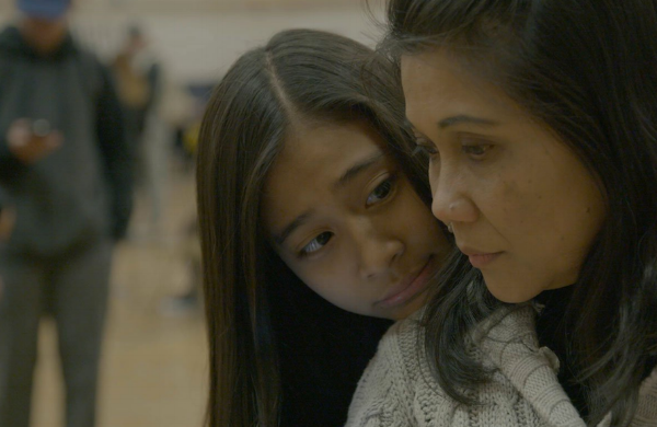 In a school gym, teenager Jeah Banico rests her head on her mother Melona's shoulder as the woman looks down.