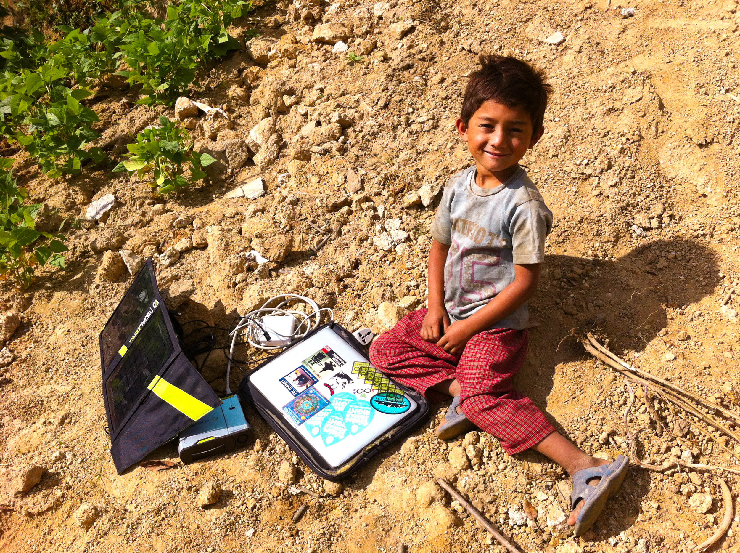 Sandesh, 5, sits with a Good Earth Volunteer's solar charger and laptop. He and his sister Nambrita enjoyed their first week time hosting volunteers thoroughly and will be attending the Agara Earthbag school upon its completion.