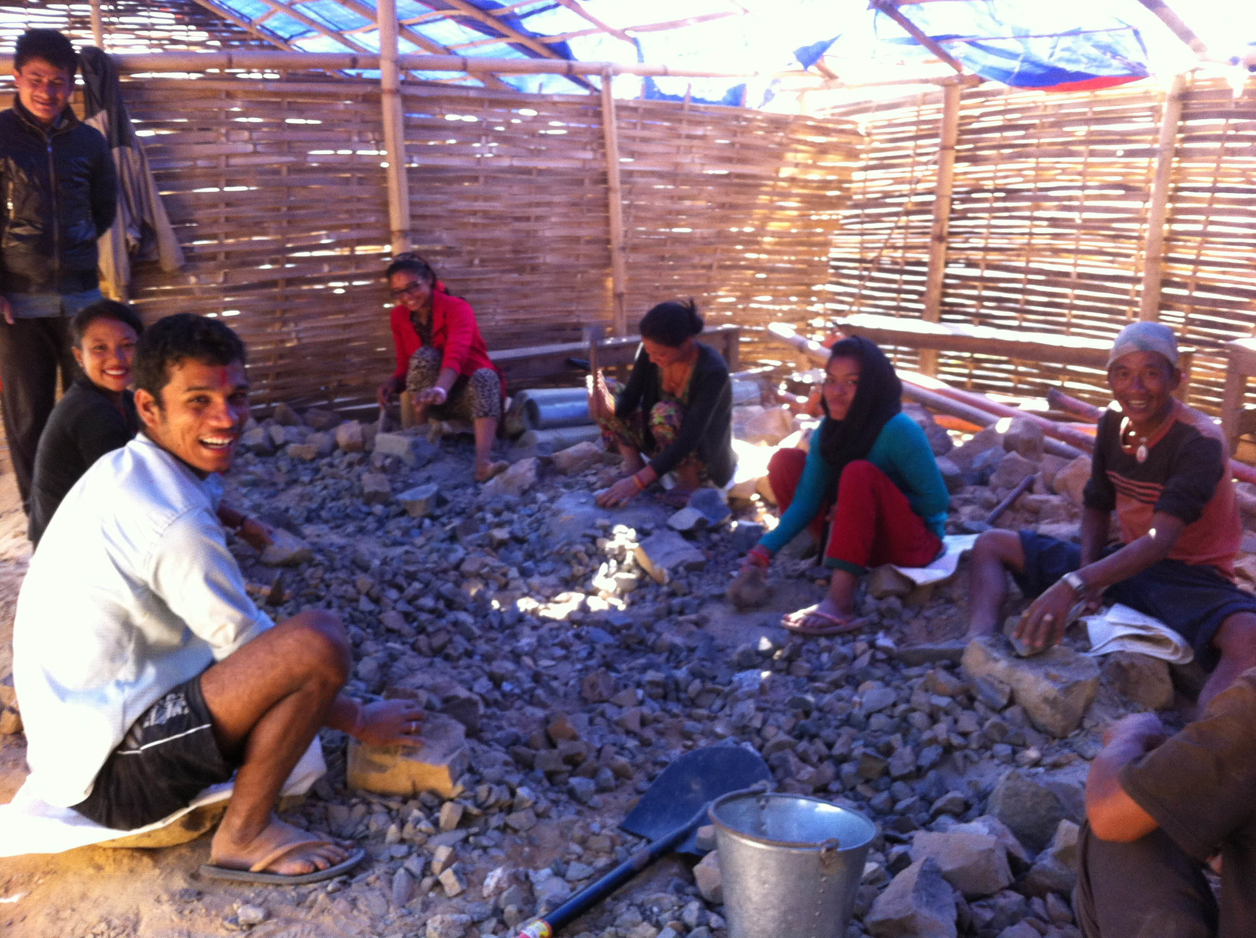 Villagers smile during a jokingly afternoon smashing rubble from the destroyed school into gravel for the new foundation.