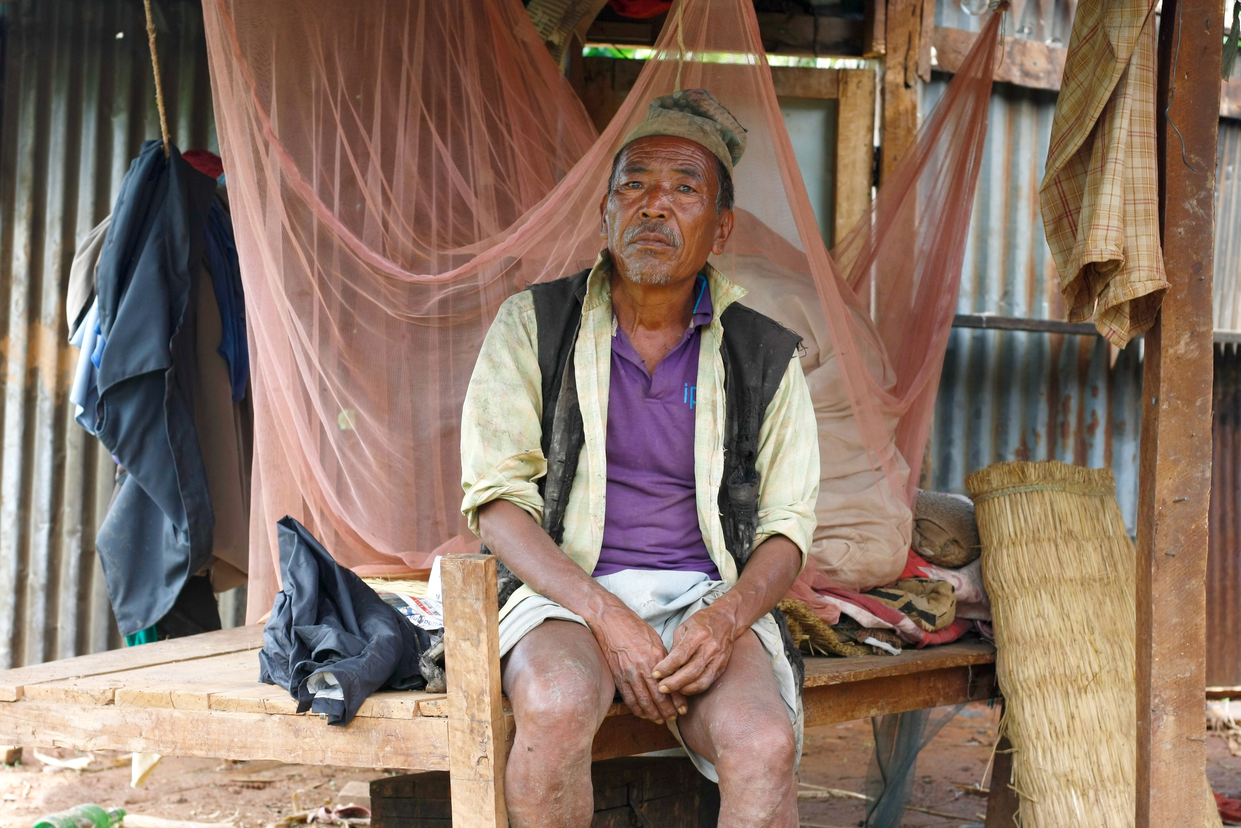 Gunda Bahadur Tamang inside his temporary shelter, sitting atop the wooden platform he uses as a bed. The pink see-through material behind him is an improvised mosquito net, a bit of ingenious craftiness to help him sleep while otherwise exposed to the elements