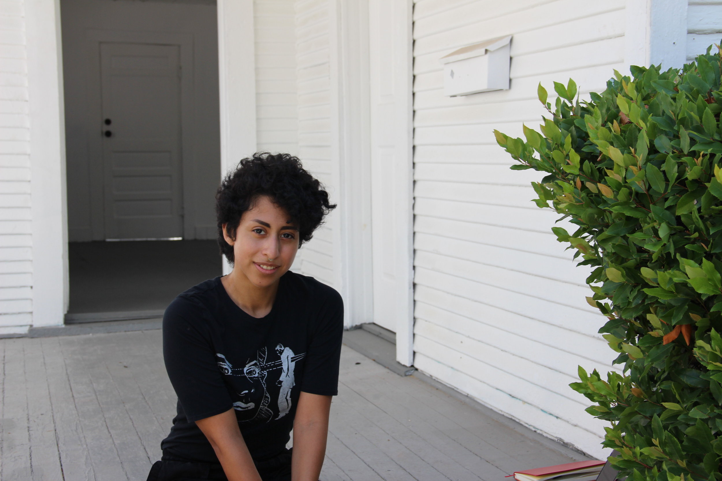 Summer Studios resident Charli Sol on the porch of their art house.