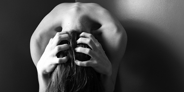Stressed and anxious woman grabbing her head and hair.